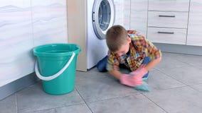 De jongen in rubberhandschoenen wast de vloer in keuken het spelen met doek Het huisplichten van het kind stock footage