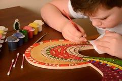 De jongen schildert de kleuren van het hout Stock Afbeeldingen