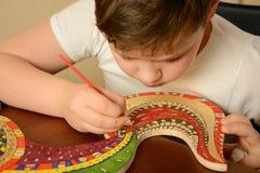 De jongen schildert de kleuren van het hout Royalty-vrije Stock Foto's