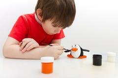 De jongen schildert een pinguïn die van zout deeg wordt gemaakt Stock Fotografie