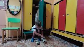 De jongen in de schoenen van kleuterschool zelf schoenen stock footage