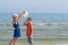 De jongen schreeuwt zuster draagt een hoed op hem Royalty-vrije Stock Fotografie