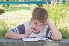 De jongen schrijft aan schrijven-boeken Stock Foto