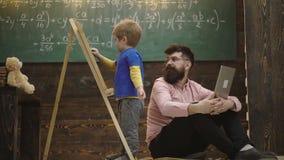 De jongen schrijft met krijt op een raad Mooie peuterjongen die op bord op houten achtergrond trekken Mensencontroles het leren stock video