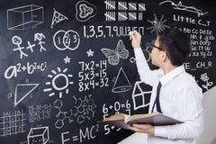 De jongen schrijft wiskundeformule in klasse Royalty-vrije Stock Afbeelding