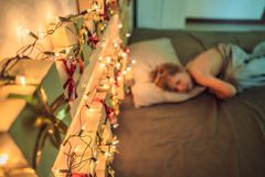 De jongen slaapt op het bed Op het hoofdeinde is een komst kalender met voorstelt en het gloeien gerland royalty-vrije stock foto's