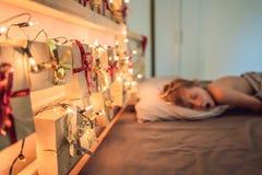 De jongen slaapt op het bed Op het hoofdeinde is een komst kalender met voorstelt en het gloeien gerland stock afbeeldingen