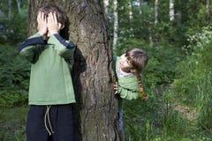 De jongen sluit zijn ogen door hand. Het meisje kijkt uit boom. Stock Afbeeldingen