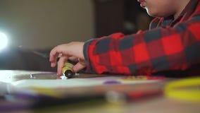 De jongen snijdt een extra stuk van ABS plastic 3D pen af Hij creeert een 3D cijfer van plastiek stock footage
