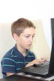 De jongen speelt de computer Stock Fotografie
