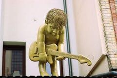 De jongen speelt een gitaarstandbeeld royalty-vrije stock afbeeldingen