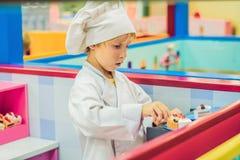 De jongen speelt het spel alsof hij een kok of een bakker in een kinderen` s keuken was royalty-vrije stock afbeelding