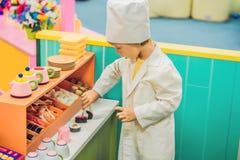 De jongen speelt het spel alsof hij een kok of een bakker in een kinderen` s keuken was royalty-vrije stock foto's