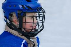 De jongen speelt hockey Stock Afbeeldingen