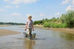 De jongen speelt met water op de banken van de rivier stock foto's