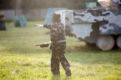 de jongen speelt paintball op het gebied twee teams van paintballspelers in camouflage vormen zich met maskers, helmen, kanonnen  stock afbeeldingen