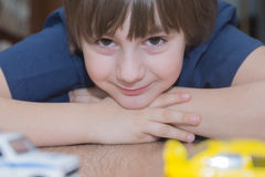 De jongen speelt stuk speelgoed auto's op de vloer Royalty-vrije Stock Foto's