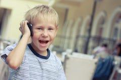 De jongen spreekt aan een mobiele telefoon Stock Afbeeldingen