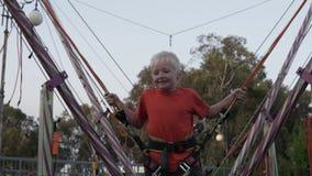 De jongen springt hoog omhoog op een trampoline stock video