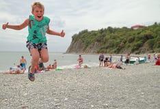 De jongen springt op het strand Stock Afbeeldingen
