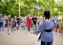 De jongen springt over een kabel door meisjes in piraatkostuums bij piraatpartij die wordt gehouden stock fotografie