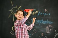 De jongen start een vliegtuig tegen de achtergrond van een schoolraad op royalty-vrije stock foto's