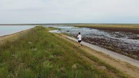De jongen stelt een landweg langs de kust van de baai in werking stock video