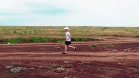 De jongen stelt een landweg langs de kust van de baai in werking stock videobeelden