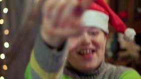 De jongen in de sweater en de hoed van Santa Claus lacht Close-up, tegen de achtergrond van Kerstmislichten stock footage