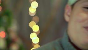 De jongen in de sweater en de hoed van Santa Claus lacht Close-up, tegen de achtergrond van Kerstmislichten stock video