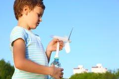 De jongen tegen hemel speelt met door de wind aangedreven generator royalty-vrije stock foto