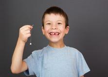 De jongen toont verloren tand op draad Stock Afbeeldingen