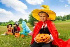 De jongen in tovenaarskostuum houdt Halloween-pompoen Stock Foto's