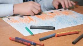 De jongen trekt beelden gebruikend kleurenkrijt en potloden stock video