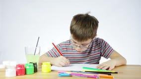 De jongen trekt een beeld van een potlood stock footage