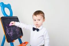 De jongen trekt een krijt op een raad Stock Foto's