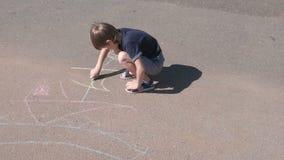 De jongen trekt een schip met blauw krijt op het asfalt Close-uphanden stock video