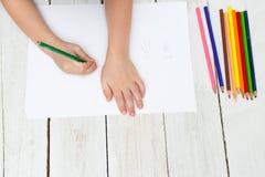 De jongen trekt kwallen met kleurpotloden op papier Vlak leg stock afbeeldingen