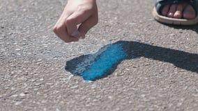 De jongen trekt met blauw krijt op het asfalt Close-uphanden stock video