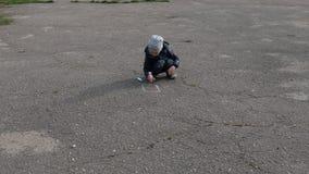 De jongen trekt met krijt op het asfalt stock video