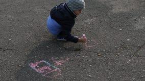 De jongen trekt met krijt op het asfalt stock videobeelden