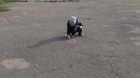De jongen trekt met krijt op het asfalt stock footage
