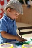 De jongen trekt met plasticine Stock Fotografie