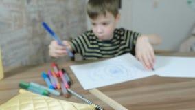 De jongen trekt ovalen met een blauwe teller op Witboek blur stock footage