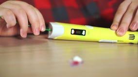De jongen van de close-uptiener neemt ABS plastiek in 3D pen op stock footage