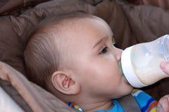 De jongen van de baby het drinken fles in wandelwagen Royalty-vrije Stock Foto