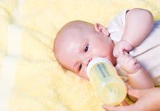 De jongen van de baby het drinken melk van fles Stock Afbeelding