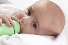 De jongen van de baby het drinken van een zuigfles Stock Afbeelding