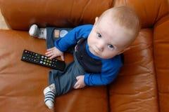 De jongen van de baby het spelen met verre TV Stock Afbeelding