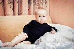 De jongen van de baby het stellen op het bed van ouders in slaapkamer Royalty-vrije Stock Afbeeldingen